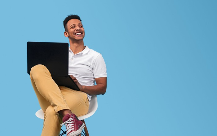 A happy-looking man sitting on a chair and looking up from his laptop.