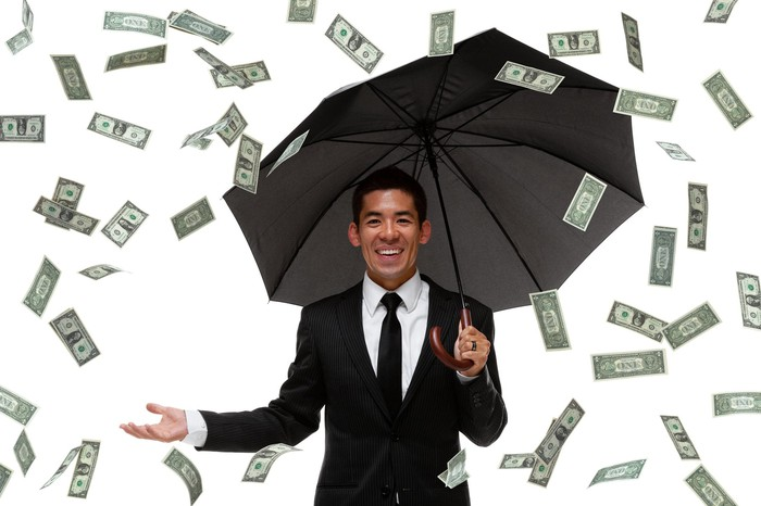 Paper money raining down on a businessman holding an open umbrella.