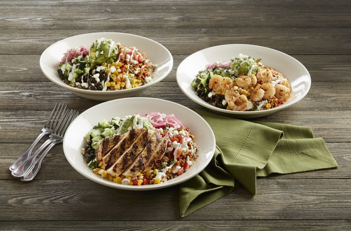 bowls holding food items from BJs Restaurants menu sit on a table with a napkin and forks