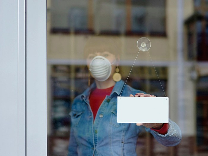 Woman in mask turns store window sign around.