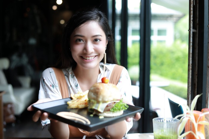 A waitress smiles while holding a tray with a burger on it.