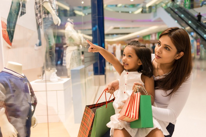 Mother and daughter window shopping in a mall.