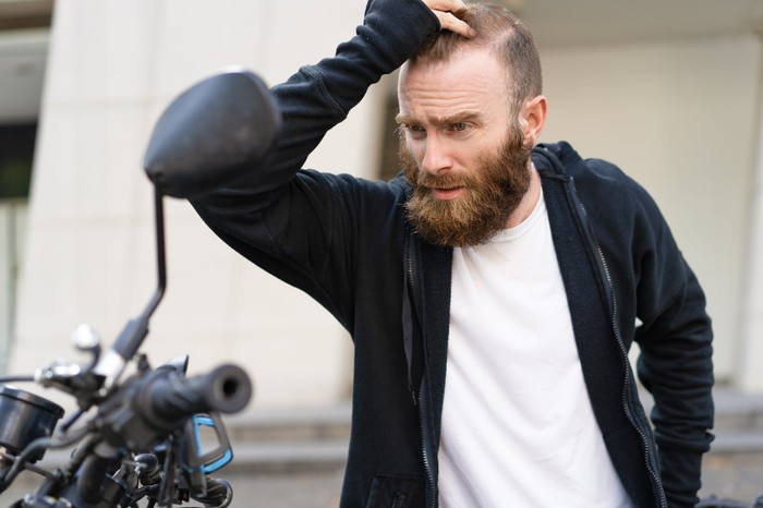 Motorcyclist looking upset over his damaged motorcycle.