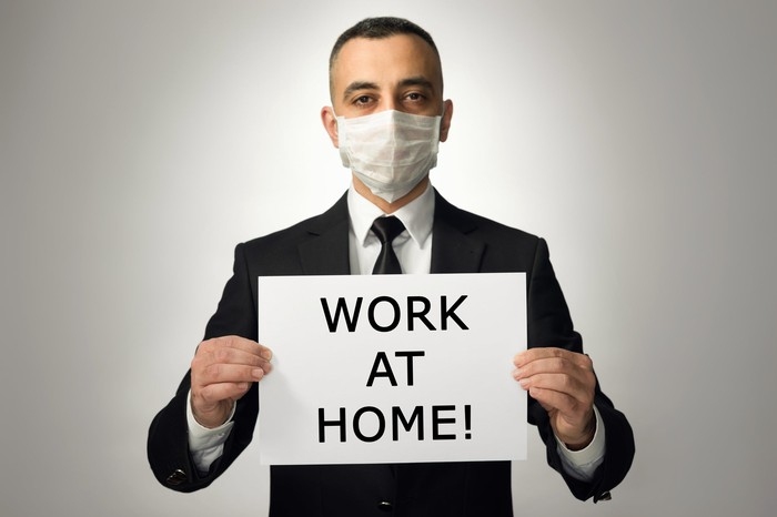 """A man in a suit wearing a protective mask holding a sign that says """"work at home!"""""""