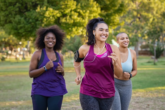 Three women are smiling while they are jogging.