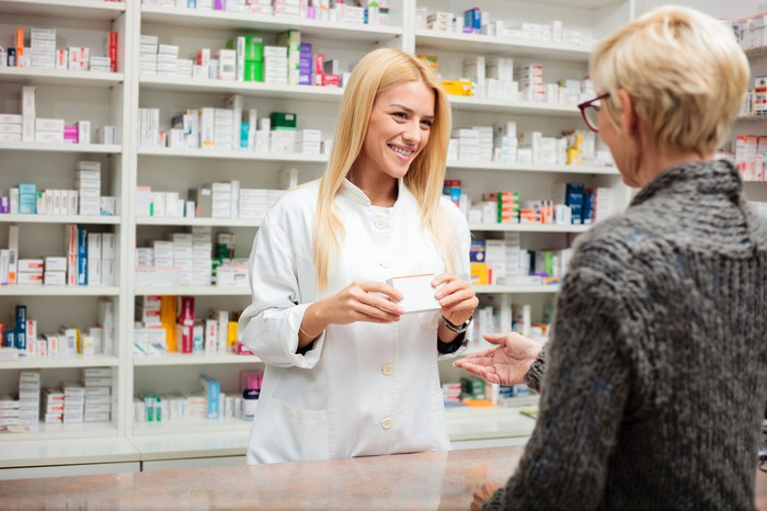 Pharmacist speaking with customer at pharmacy counter