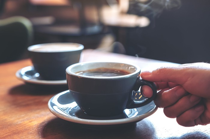 Two cups of coffee on a table.
