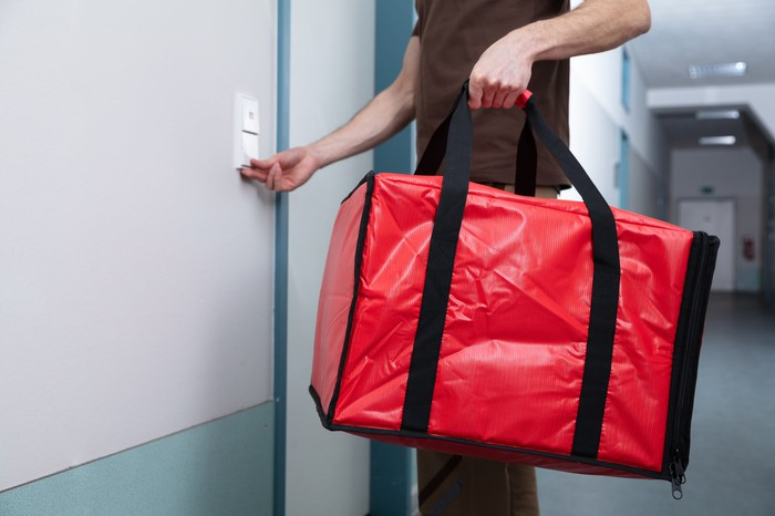 A delivery person rings a door bell while carrying a red bag containing meals.