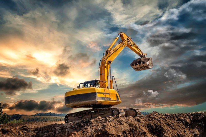 earth moving caterpillar equipment working against a setting sun
