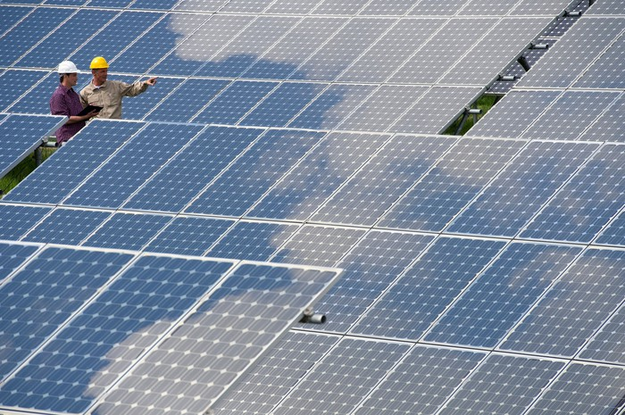 Two engineers stand among an array of solar panels.
