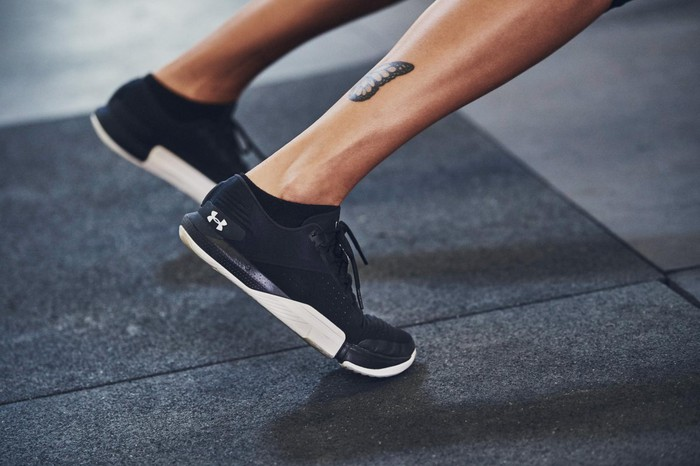 The feet of an athlete stretching in Under Armour shoes