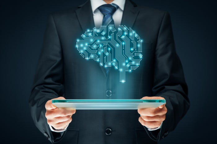 Someone in a suit pictured offscreen holding a computer monitor. A brain made of electrical connections hovers above it, illustrating AI.
