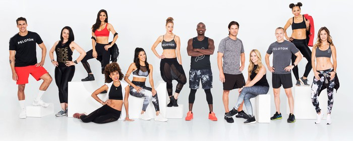 Peloton trainers pose in a group photo.