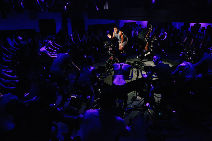 An instructor on a stationary bicycle leads a Peloton group fitness class in purple mood lighting.