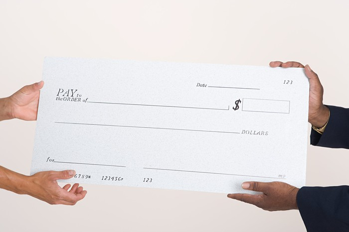 Large blank check being held by two people