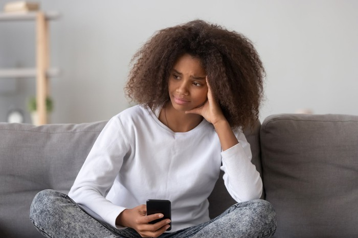 Young woman sitting at home with a phone in her hand.
