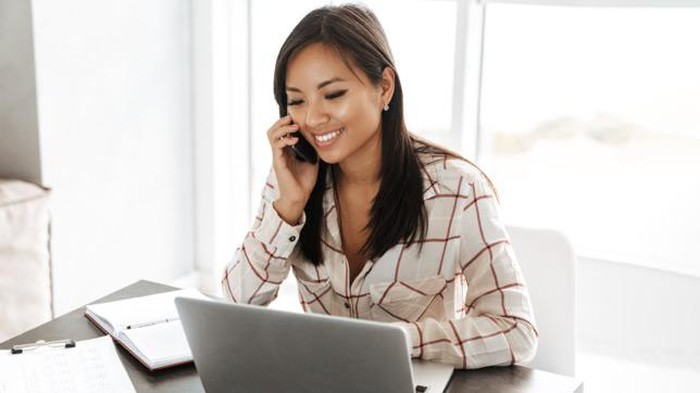 A woman talks on the phone while sitting at her laptop.