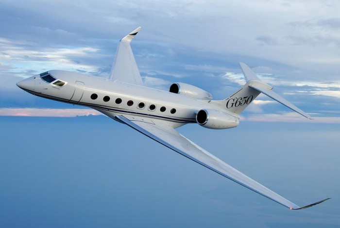 A Gulfstream G650 in flight over water.