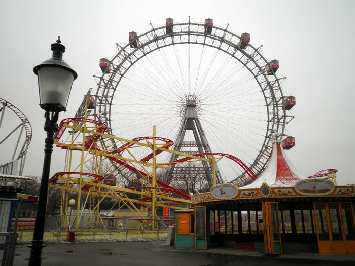Photo of a ferris wheel and roller coaster in an abandoned theme park.