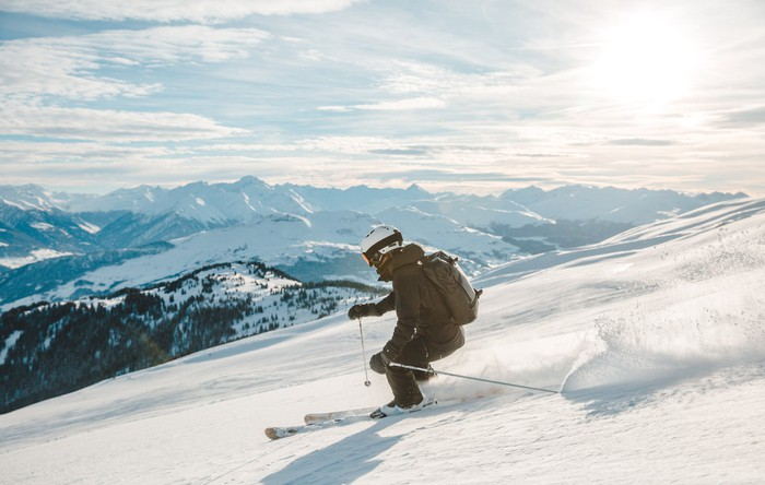 A skier racing down a mountain with the sun in the background.