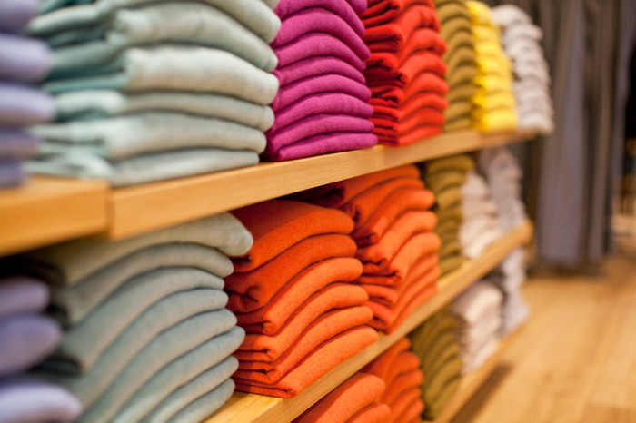 Sweaters in gray, pink, orange and other colors are stacked on store shelves.