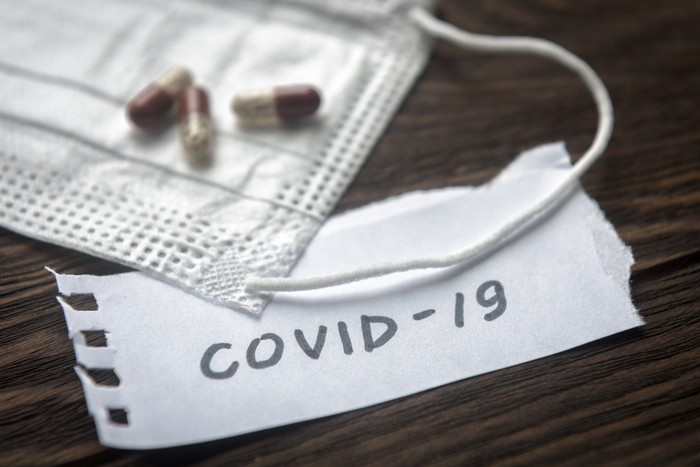 Pills and a mask are set on a wooden surface with 'COVID-19' written on a piece of paper.