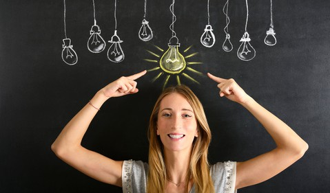 19_07_30 a woman pointing to a lit chalk lightbulb above her head_GettyImages-492784636