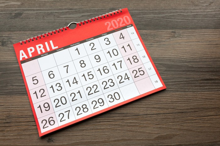 A calendar turned to April 2020 on a wooden desk.