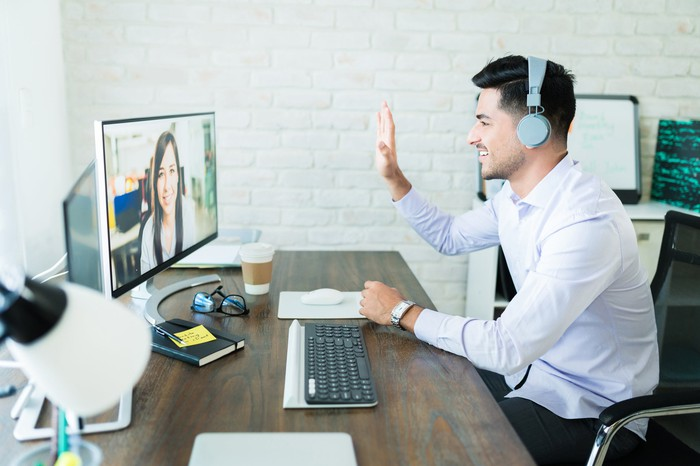 Man wearing headphones and waving to lady on monitor