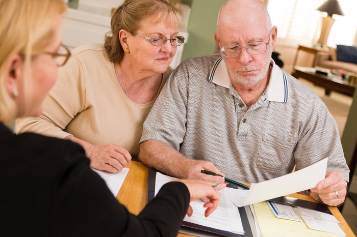 Older senior couple looking at paperwork with financial advisor.