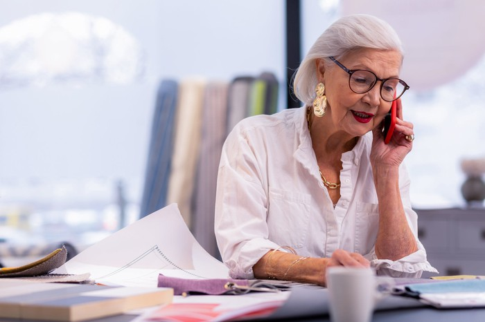 Older working woman sitting at her desk and talking on the phone.