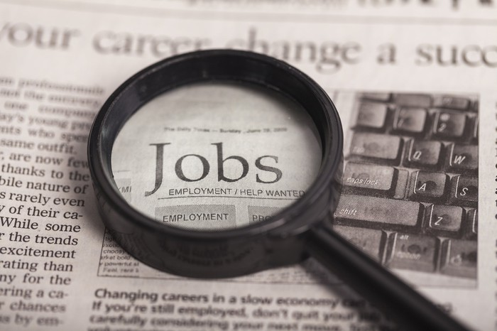 Resting on a newspaper, a magnifying glass focuses on the word jobs.
