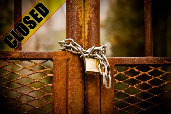 A lock and closed sign on a factory metal gate.