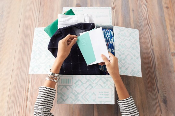 A woman opening a delivery from Stitch Fix