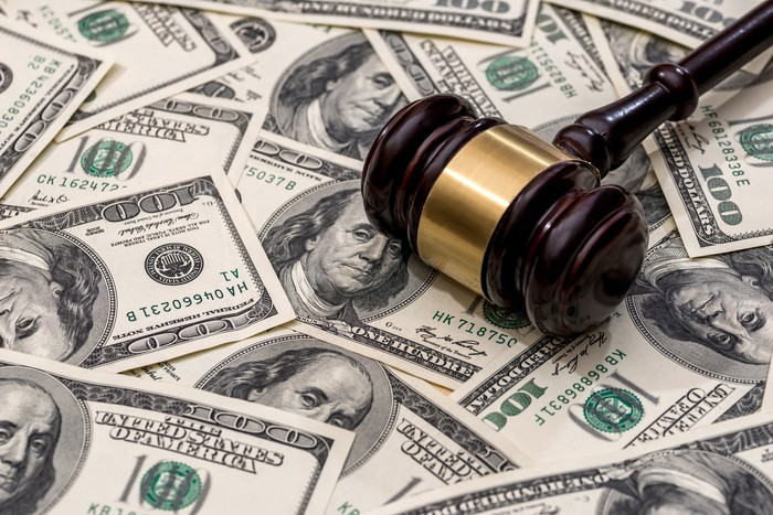 A judge's gavel on a background of $100 bills.