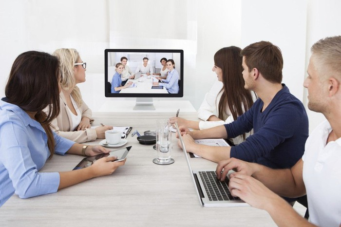 Five people in a meeting looking at five other people on a videoscreen