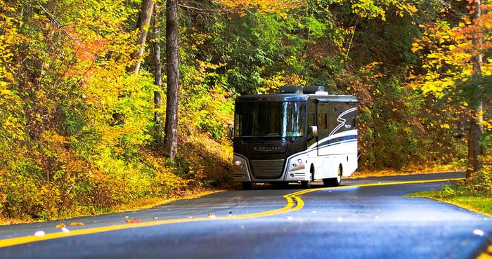 Winnebago Adventurer RV on a forest road.