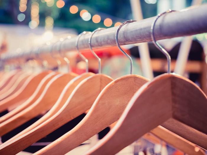 Wooden hangers on a discount fashion store clothing rack.