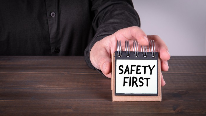 A businessman places a small sign on a table, reading Safety First.