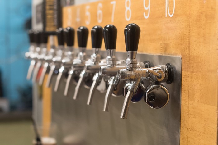 Close-up of ten draft beer taps at a brewery.