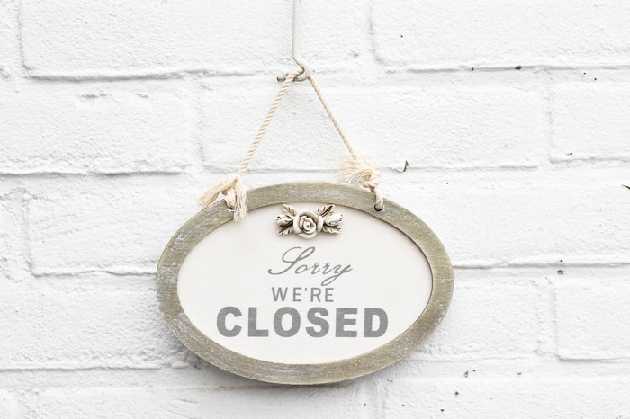 Sorry we're closed sign hung on a white brick wall.