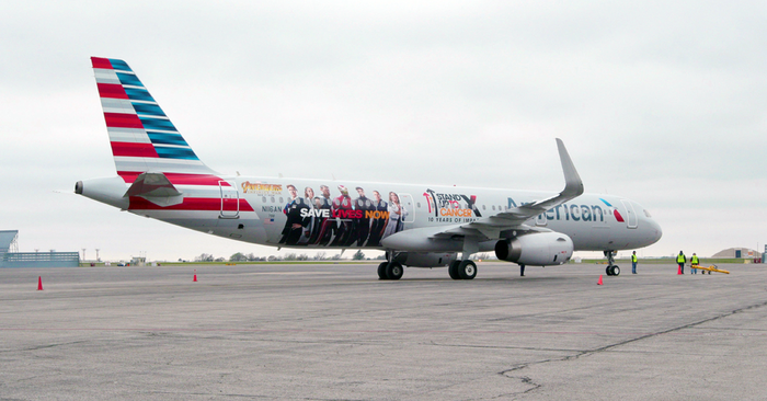 Airplane on apron with American markings and logo.
