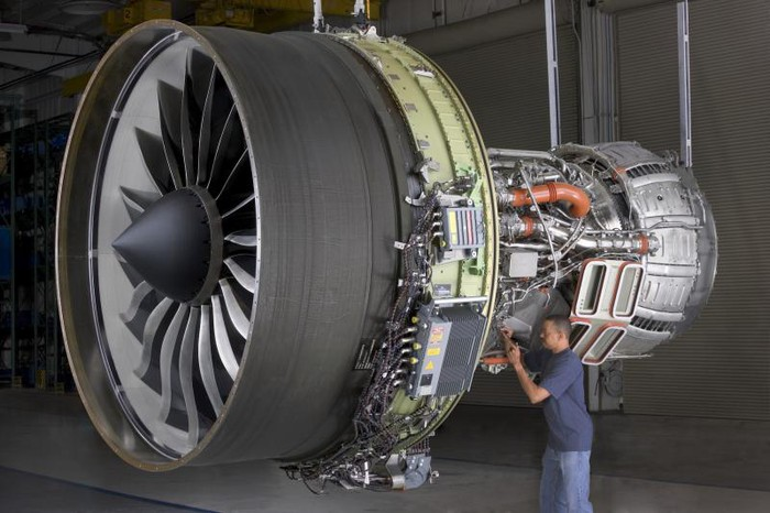 A man stands next to an aircraft turbine that's under construction.
