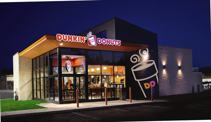 The exterior of a Dunkin' Donuts restaurant at night.