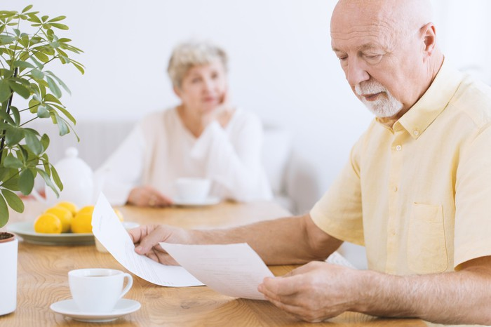 Older man looking at documents with blurry image of older woman in background