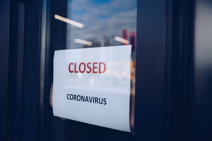 A sign reading CLOSED coronavirus in a shop window.