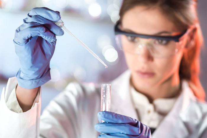 A biotech researcher in a lab holds a pipette and test tube in gloved hands.