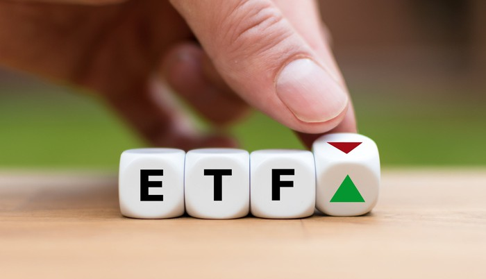 Dice that spell out ETF on a wooden table top, with a hand turning a fourth die from a down red arrow to an up green arrow.