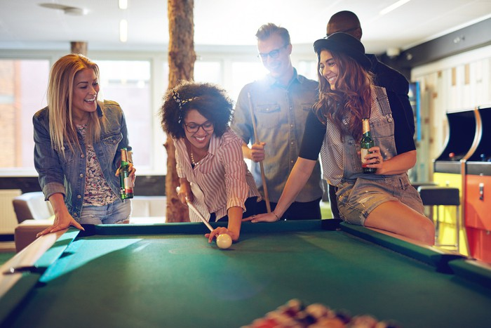 A group of people playing pool in an arcade.