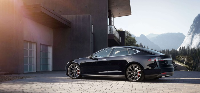 Tesla Model S in a driveway with a mountainous background.